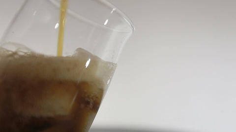 Cola with ice. Pouring Cola with Ice and bubbles in glass Live Action
