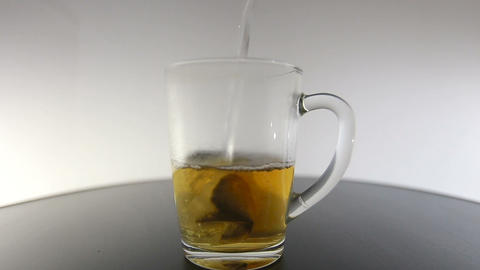 Pouring hot water over tea bag in glass cup Footage