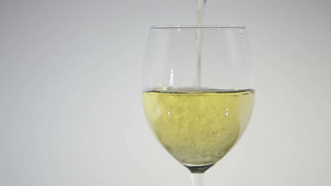 Pouring white wine from the bottle into a glass Footage