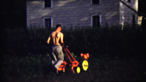 1959: Shirtless man mowing thick weeds lawn with industrial machine Footage