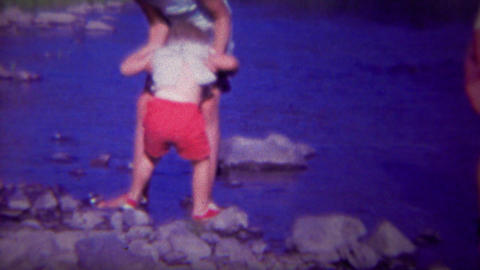 1966: Toddler wades into river water help from big sister Footage