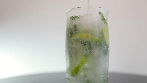 pouring soda in mojito on white background Footage