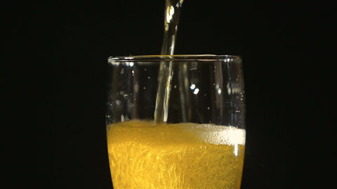 Beer poured in glass with bubbles on black background Footage