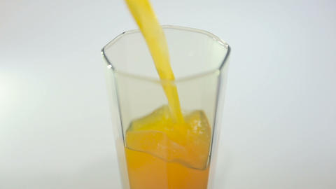 Pouring Juice In Glass On A White Background.shot From The Top stock footage