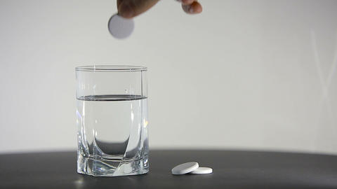Aspirin or effervescent pill dropping into a glass of water on white background Footage