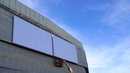 Man erects billboard poster for advertising. Blank wall for copy space Archivo