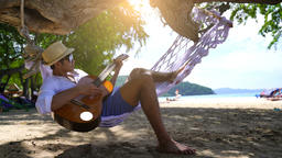 Happy playing guitar at the beach GIF