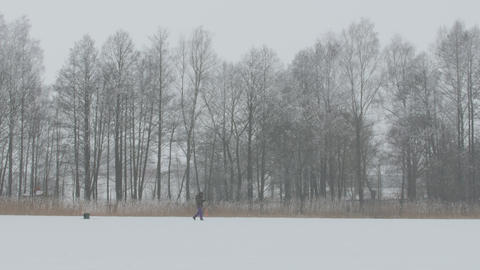 Winter fishing. Lonely fisherman sitting on ice fishing Image