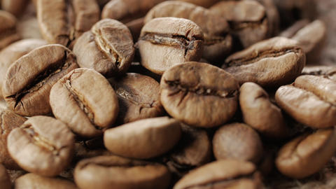 A handful of brown, roasted coffee beans on burlap sacking background, close up Footage