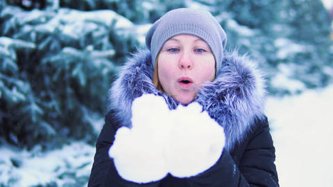 girl blowing snow with her hands, slow shooting, winter snow-covered park with Footage