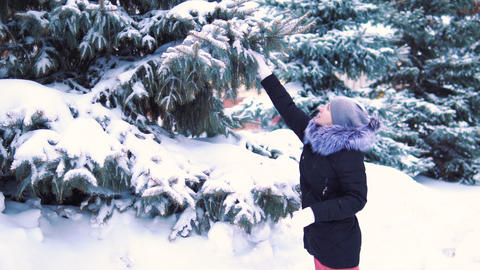 snow falls from tree to girl, slow-motion shooting, winter snow-covered park Footage