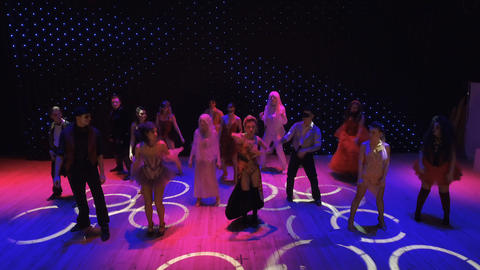Actors in bright costumes are dancing and singing at the colorful stage Footage