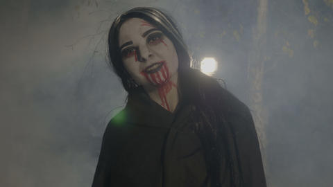 Bloody evil female vampire enjoying the foggy halloween night in the woods and Footage