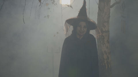 Silhouette of a black female witch playing with her hat on halloween night Footage