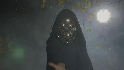 Spooky dark zombie wearing a mask playing with his black cape attacking the Footage
