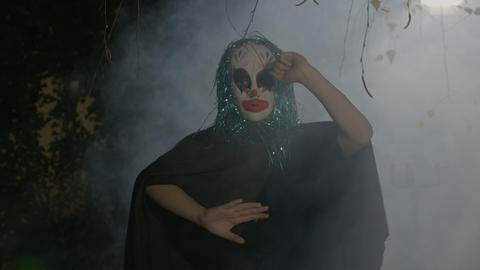Insane evil halloween clown mime miming a slowly death between walls in darkness Footage