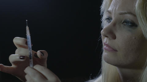 Portrait of a young female preparing syringe with heroin to surpass depression Footage