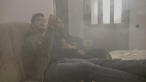 Stressed junkies male sitting in a dope house room full of smoke while inhaling Footage