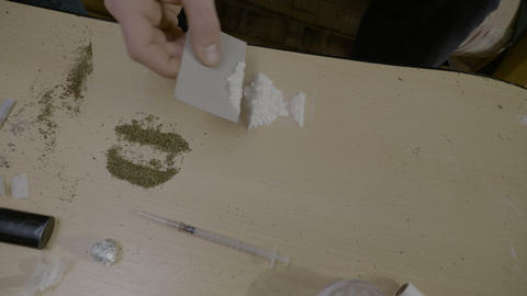 Close up of a table with marijuana and heroin shot on it and a male hands Live Action