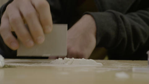 Close up of a narcotic young father snorting cocaine from the table while his Footage