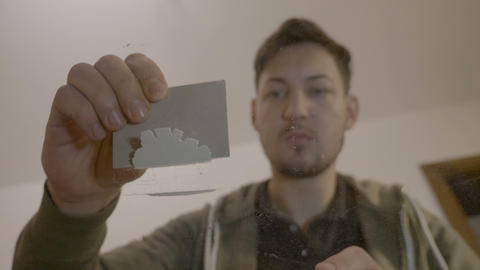 Portrait of a young narcotic man scraping cocaine powder with a thick card on Live Action