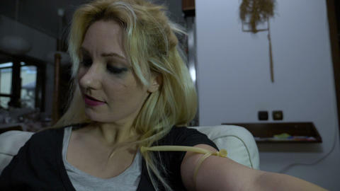 Drug addicted single mother preparing her shot of heroin and injecting it into Live Action