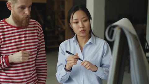 Cheerful asian girl explaining start-up project on flipchart to hipster male Footage