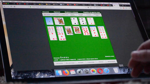 Man playing computer game Solitaire on the monitor computer close-up Footage
