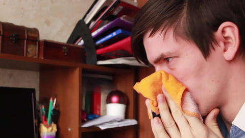 young guy has a runny nose, wipes his nose with a handkerchief, sneezes into his GIF