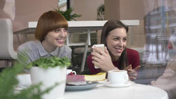 Three young caucasian girls are sitting in a cafe, laughing, smiling, friends Footage