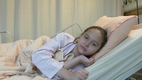 Happy Asian American tween girl in hospital bed Footage