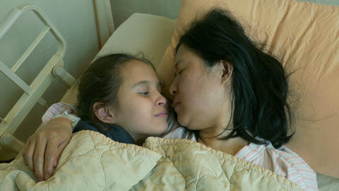 Happy child kissing mother in hospital bed Live影片