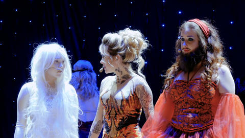 Fire girl sings song to bearded girl and albino girl on the stage in theatre Footage