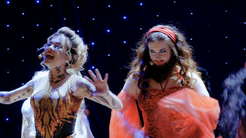 The actors in crazy costumes are singing and dancing on the stage in theatre Footage