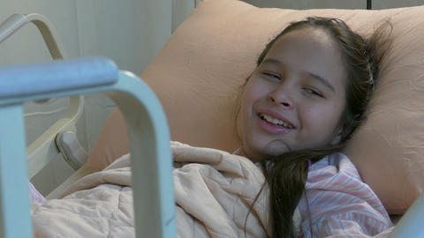 Asian American tween girl in hospital bed laughing Footage
