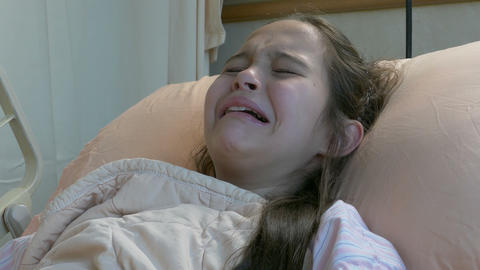 Asian American tween girl in hospital bed showing pain upset screaming crying Footage