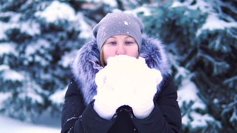 girl blowing snow in a winter park, smiling and enjoying the snow, slow motion Footage