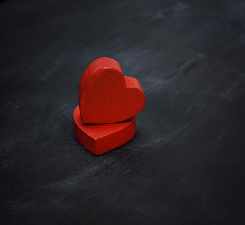 two red wooden hearts on a black background Photo