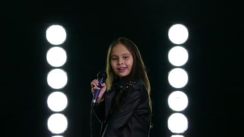 Young girl singing with microphone on stage GIF 動畫