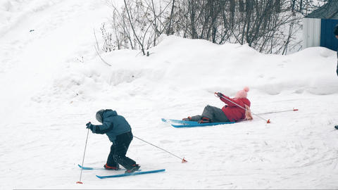 Boy and a girl are skiing under the care of their mother Footage