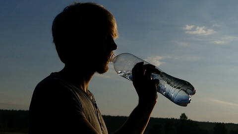 Blond man drinks water from a plastic bottle at sunset in slo-mo Footage