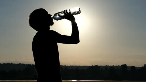 Stylish man drinks water from a plastic bottle at sunset in slo-mo Footage