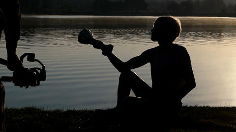 Young man sits on a lake bank and looks at a winner bowl in slo-mo Live Action
