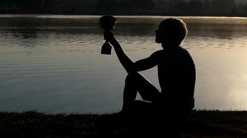 Sportive man sits on a lake bank looking at a winner bowl in slo-mo Image