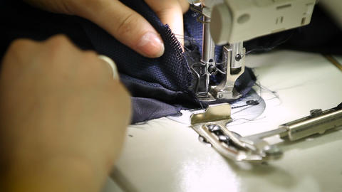 Stitching several pieces of fabric into one piece Live Action