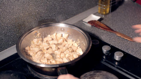 Close up of a frying pan as a chef tosses the pan and stirs a sri lankan chicken Live Action