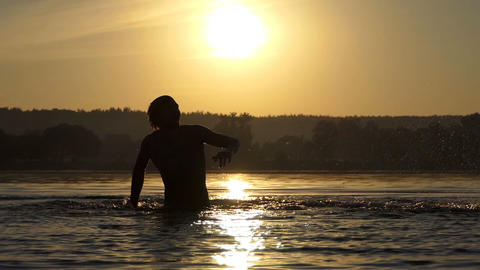 Hilarious man beats the lake water to entertain at sunset in slo-mo Footage