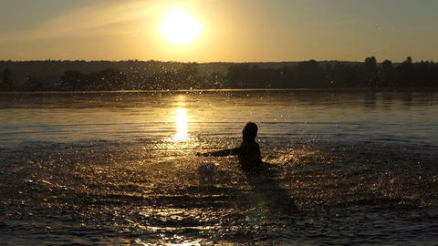 Funny man makes circles in a lake to enjoy at sunset in slo-mo Footage