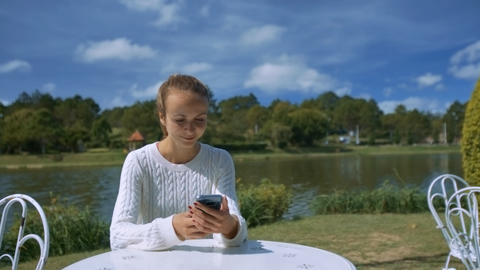 Girl Writes Sms Sitting at Cafe against Landscape Live Action