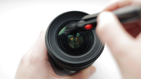 The photographer or videographer cleans front lens from dust and dirt with the Footage